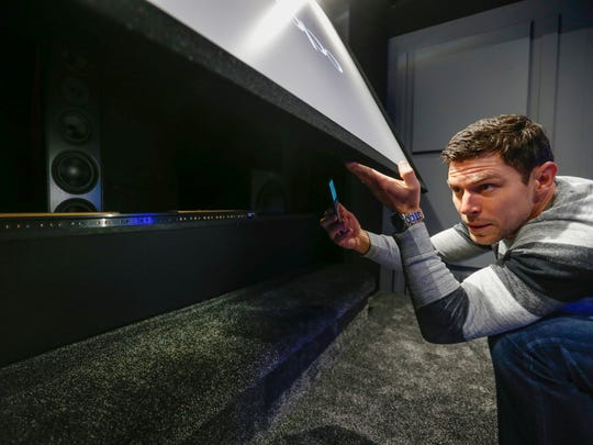"Patrick Williams lifts the screen to show the subwoofers in his ""Star Wars""-themed home theater at his home in Nixa."