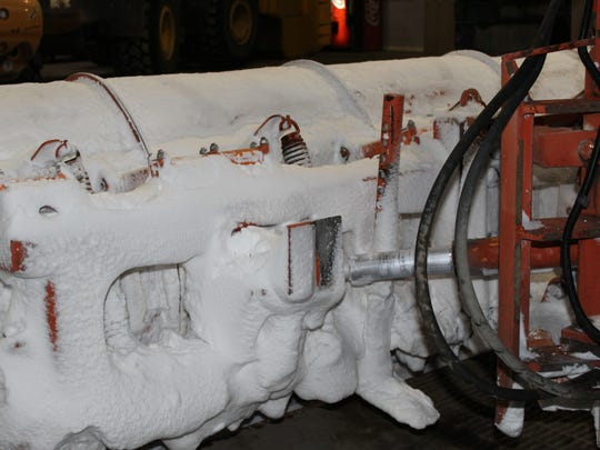 Snow and ice are caked onto the backside a snow-blade following the eight-hour night shift
