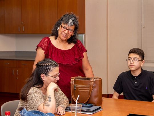 Trine Lane, 45, (left) and Brannden Fernandez, 14, (right) talk with transplant group president Lupe Jimenez, 57, (center) at the transplant group meeting at Mountain View Regional Medical Center.