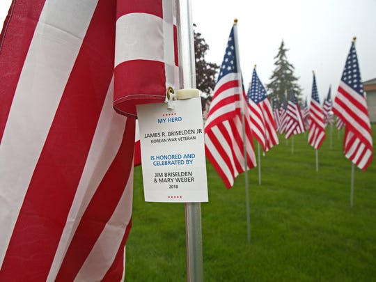 A flag bears the name tag of a hero and the people whose lives were touched by the hero.