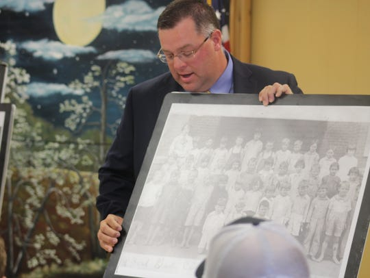 Trevor Fry holds a photo of Colfax High School students,