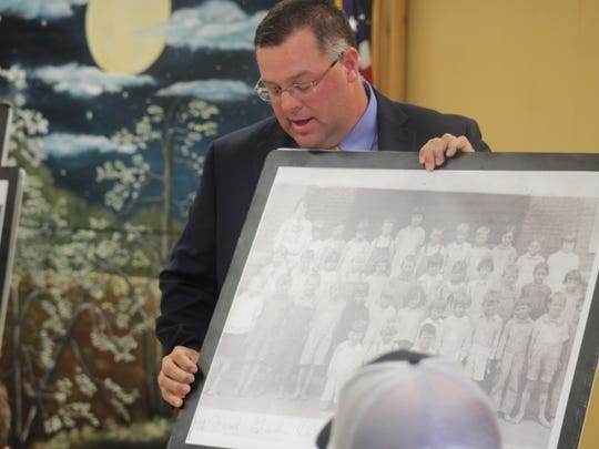 Trevor Fry holds a photo of Colfax High School students, including James E. Valentine at the lower left corner. Valentine, a Colfax native, died as a Japanese prisoner of war during World War II.