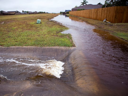 Rainwater flows from waterlogged lawns and roadways in the Country Creek subdivision on the Southside into a drainage ditch. The rain began early Tuesday morning and continued throughout the day, June 19, 2018.