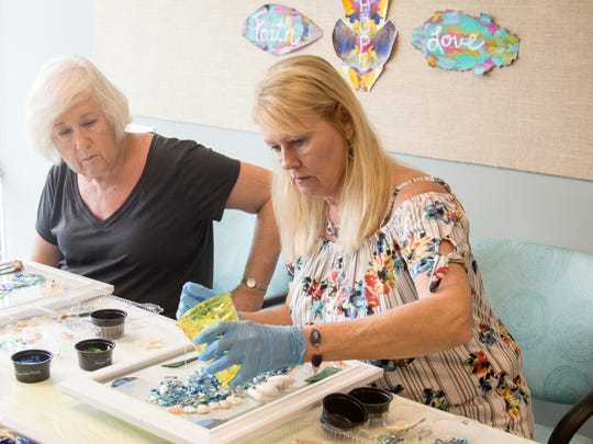 "Sue Marcinko, left, watches as artist Christine Fitzgerald applies a nontoxic resin to a student's art. ""I love it,"" said Fitzgerald of being a part of the inaugural class. ""It's my passion to teach, so I love being here today."""