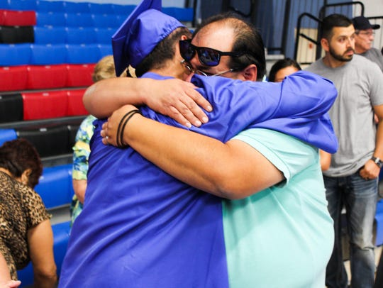A graduate hugs a family member after receiving his