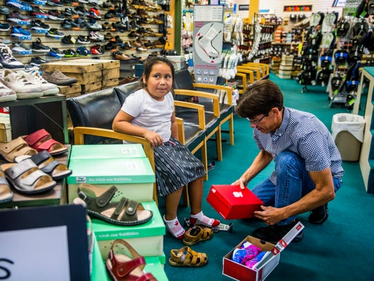 Chris Bossi, store manager, helps incoming second-grader Melina Lopez, of Immokalee, try on a pair of shoes at Snyderman's Shoes of Naples on Tuesday, July 10, 2018. Throughout this week, 250 kids from the Guadalupe Center in Immokalee will receive a new pair of shoes for the upcoming school year. This annual event is done through a partnership with Snyderman's Shoes and Laces of Love, a nonprofit that provides new shoes to low-income kids in Collier and Lee counties.