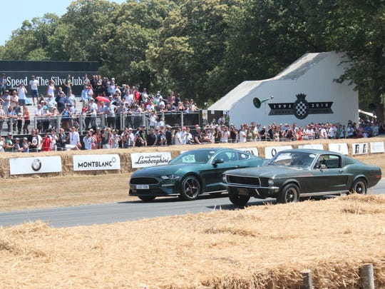"""The 2019 Mustang Bullitt rolls alongside the 1968 Mustang fastback, used in the Steve McQueen film """"Bullitt,"""" at the 2018 Goodwood Festival of Speed held near Chicester, England."""