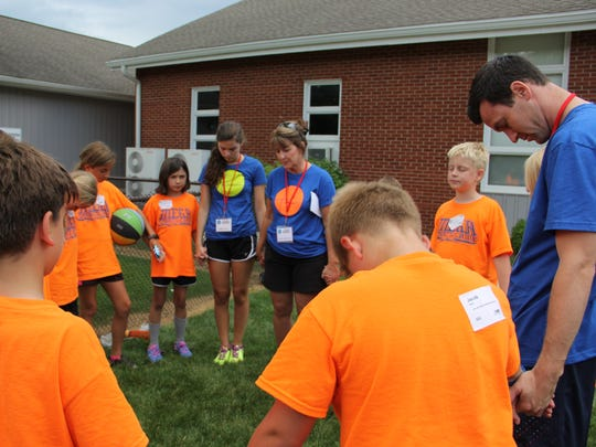 Prayer and bible stories are part of the experience for participants in the MEGA Sports Camp at People's Church in Pinckney.