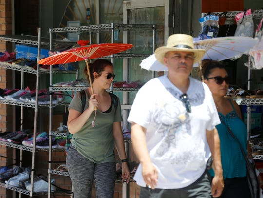 Shoppers use umbrellas for bit of relief from the sun