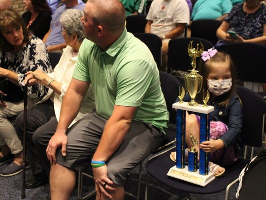 "Elliana Nelson, 6, sits with her trophy at Ontario City Council on Wednesday, Aug. 1, 2018. A photo of Elliana, who has a rare disease, won the ""Can You Picture Ontario"" photo contest."