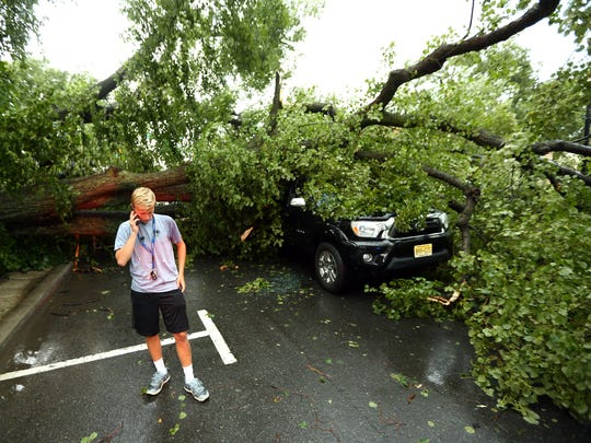 Morristown teen, Kyle Gehsmann talks to his mother after escaping through his damaged driver side door shaken but uninjured after a violent afternoon storm uprooted a large tree in front of St Peters Episcopal Church onto the roof of his car.  August 3, 2018. Morristown, NJ