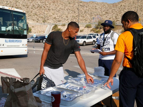 Members of the UTEP football team load their luggage