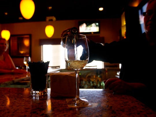 Cibo bartender Pinar Asal pours a glass of wine for a customer.