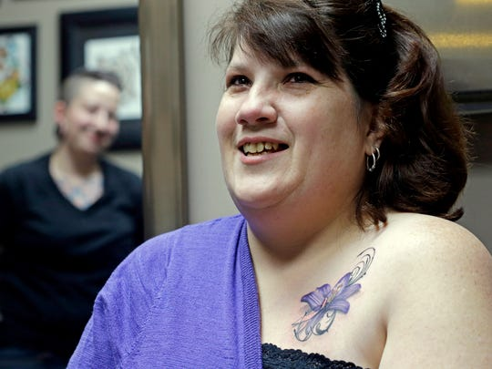Tattoo artist Ashley Neumann, left, watches as breast cancer survivor Mari Jankowski smiles as she talks about her new tattoo in West Allis, Wis. For women who have survived breast cancer, reconstructive surgery can be a first step toward looking like their old selves. The P.ink organization is helping some of those women with a step in their emotional healing - through tattoos to help conceal their scars.