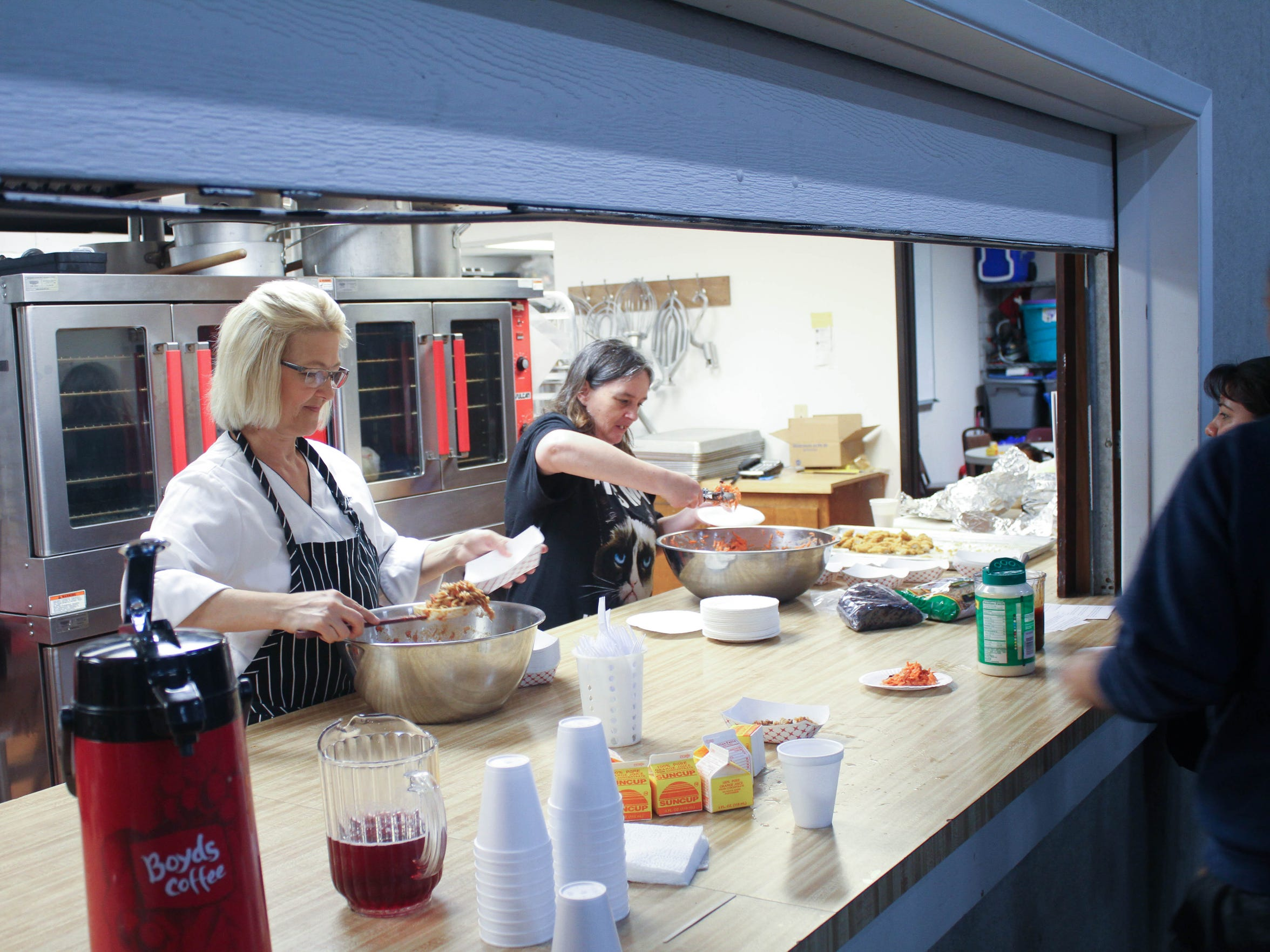 Kim Banick and other volunteers cook and serve meals