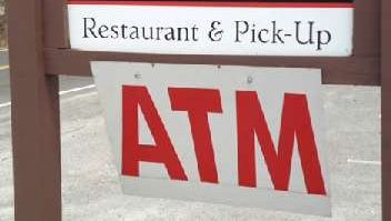 A sign lets people know the location of an Automated Teller Machine.