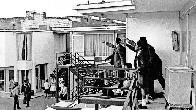 Martin Luther King Jr. is laid on a balcony after he was shot by an assassin's bullet as his aides point out to police where they heard the shot come from in Memphis on April 4, 1968.