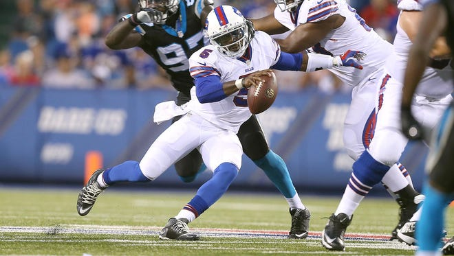 Bills quarterback Tyrod Taylor slips past the pressure by Carolina's Mario Addison in a preseason game.