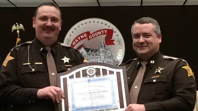 Lt. Travis Isaacs, assistant jail commander, and Capt. Andy Abney-Brotz, jail commander, hold the plaque awarded for the Wayne County Jail earning legal-based accreditation from the National Institute for Jail Operations.