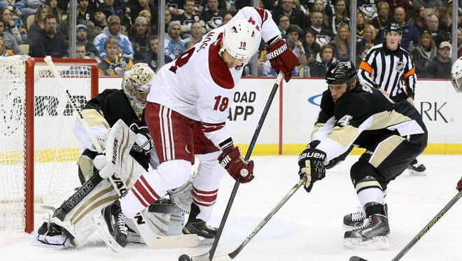Arizona Coyotes right wing David Moss (18) shoots the puck against Pittsburgh Penguins goalie Thomas Greiss (1) as Penguins defenseman Rob Scuderi (4) defends during the first period at the CONSOL Energy Center.