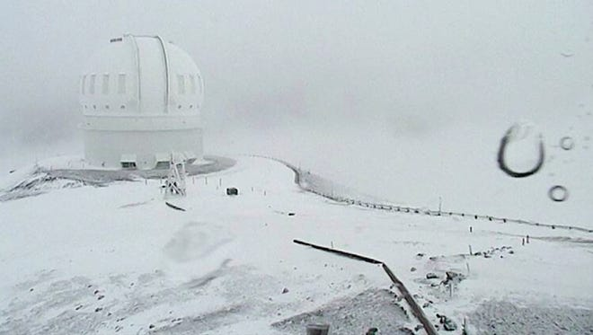 In this image made from webcam video provided by Canada-France-Hawaii Telescope, the CFHT telescope on the summit of Mauna Kea on Hawaii's Big Island is covered in snow on Thursday, Dec. 1, 2016. The National Weather Service in Honolulu has issued a winter storm warning for the summits of Hawaii's Big Island as wind and snow engulf the high peaks.