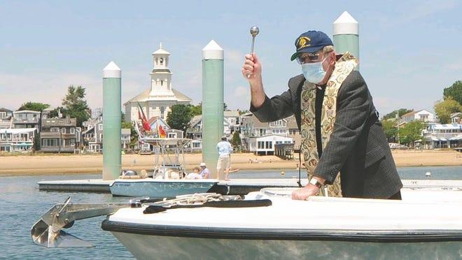O Rev. Mick McCullough, da Igreja de São Pedro Apóstolo, borrifa água benta num barco durante a Bênção da Frota, no domingo passado, em Provincetown.