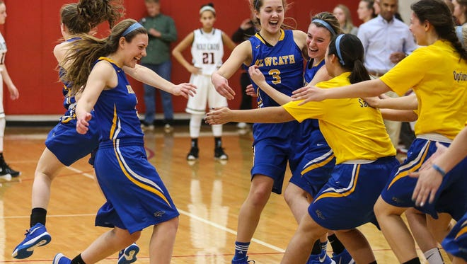 NewCath players celebrate winning the Ninth Region All A Championship game against Holy Cross, 52-50, in overtime, at Beechwood, Saturday, January 16, 2016.
