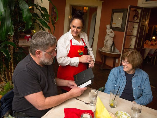 Double Eagle waitress Shannon Barrio, center, hands a meal check to Bob Hodge while friend Carol Kreitner looks on.