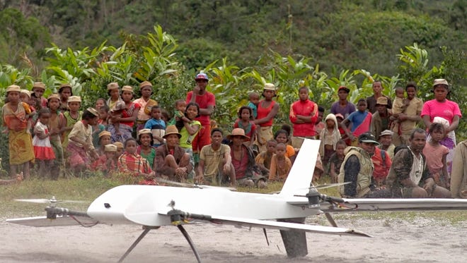 Residents from Ranomafana, Madagascar, watch July 27, 2016, before a drone containing medical samples takes off on a test flight from their remote village, which can only be reached on foot. Off Africa's eastern coast in Madagascar, U.S. company Vayu completed drone flights to deliver blood and stool samples from rural villages, with support from the U.S. Agency for International Development. (Stony Brook University/Vayu Inc. via AP, File)