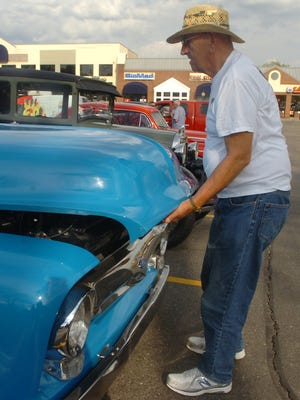 Carl Walock of Farmington Hills pops the hood to his 1954 Blue Ford F-100 pickup truck at Cruis'n the Grand on Monday.