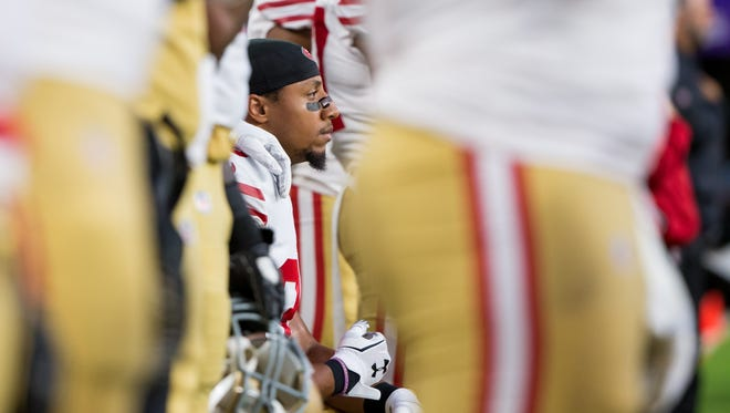 San Francisco 49ers defensive back Eric Reid kneels during the national anthem before the game against the Minnesota Vikings at U.S. Bank Stadium in Minneapolis.