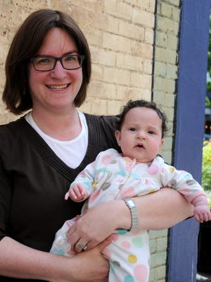 """Fruma Perlstein holds her 3-month-old daughter Rosa as she invites the public to hear a """"Harrowing Story of Survival"""" given by a Holocaust survivor, Dr. Jacob Eisenbch on Thursday night."""