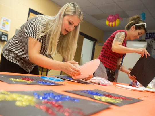 Alexis Lingner helps kids with an arts and crafts project in the Des Moines public schools Metro Kids program at Brusker Elementary School, Thursday, June 30, 2016. The 17-year-old East High student went from minimum wage to $11.73 an hour by switching jobs in June.
