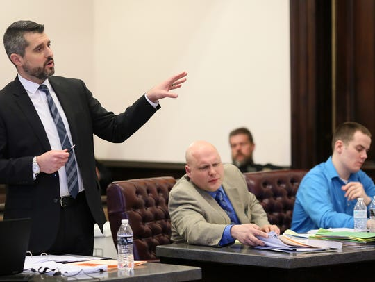 Coshocton County Prosecutor Jason Given, left, questions