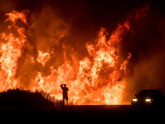 In this Dec. 6, 2017 photo, a motorist who stopped along Highway 101 watches flames from the Thomas fire leap above the roadway north of Ventura. The huge wildfire that burned hundreds of homes in Santa Barbara and Ventura counties is now the largest in California's recorded history.