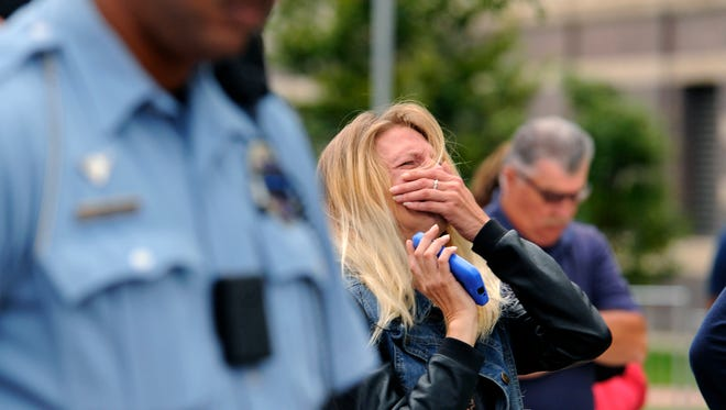 Kristina Rodeman-Brower, cousin of deceased Lansing Fire Department firefighter Dennis Rodeman, cries during a prayer for the fallen firefighter Friday morning  9/11/2015 during the emotional ceremonies honoring  Rodeman and also marking the 9/11 terrorist attacks.