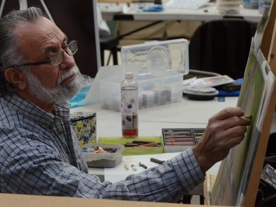 Sam Medbius works on a pastel.