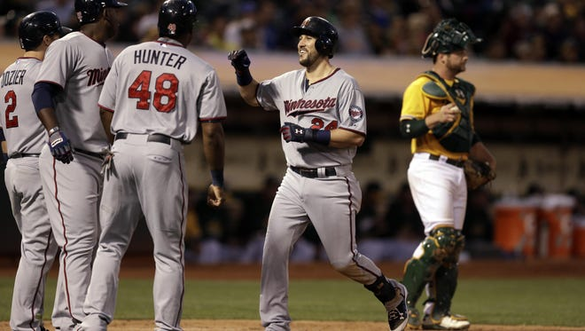 From left, Minnesota Twins' Brian Dozier, Miguel Sano, and Torii Hunter celebrate with Trevor Plouffe after Plouffe hit a grand slam off Oakland Athletics' Sonny Gray during the sixth inning of a baseball game Friday in Oakland, Calif.