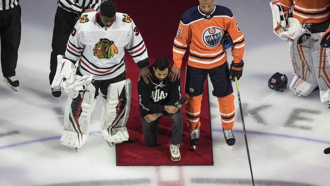 Minnesota Wild's Matt Dumba takes a knee during the national anthem flanked by Chicago Blackhawks' Malcolm Subban, left and Edmonton Oilers' Darnell Nurse before a Stanley Cup playoff game Saturday in Edmonton, Alberta. (Jason Franson / AP via]