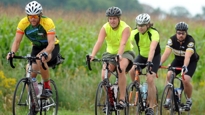 A group of bicyclists ride past the cornfields on DeWitt Road near Lansing during the DALMAC ride in August.