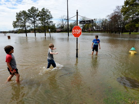 (Left to right) Mark Copenhaver, Ryder Adams, and Keegan Clark walk in the high waters that cover Lake Side Drive in Haughton, Louisiana Thursday afternoon.