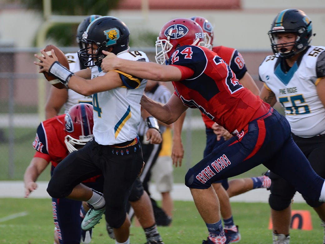 Quarterback Dillone Torres of Pine Ridge gets pulled down for a loss by linebacker David Aumuller Friday night at Cocoa Beach High School.
