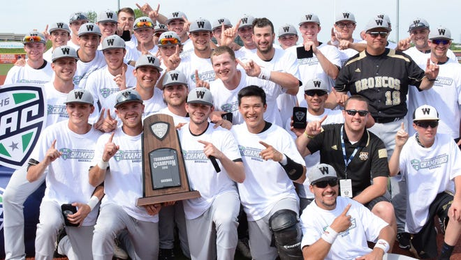 Western Michigan players pose for photos with the MAC championship trophy.