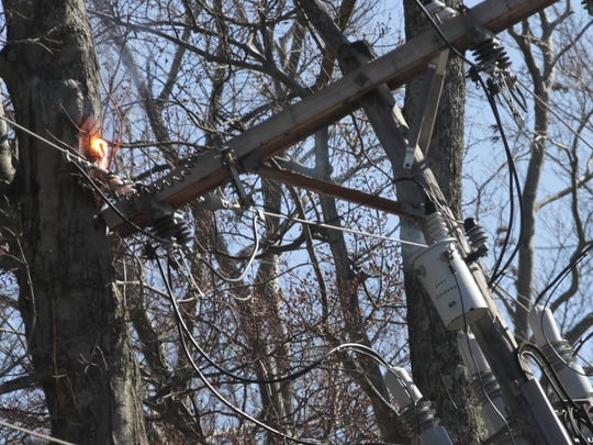 A power line arcs and makes contact with a tree on North Ford Road in Madison Township on Wednesday afternoon. High winds in the area crippled many trees and power poles.