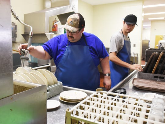 Todd Walker, right, and Brandon Coder work in the dish room of the Coshocton County Career Center. The career center is one place clients of Coshocton County Board of Developmental Disabilities has found employment in the community.