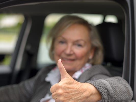 Elderly woman in a car with thumb up