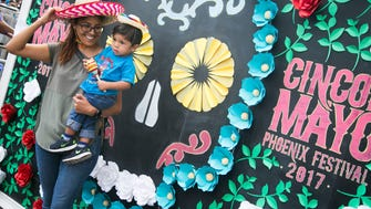 People take their picture in front of the Cinco de Mayo board at the Cinco de Mayo Phoenix Festival on May 7, 2017 in downtown Phoenix, Ariz.