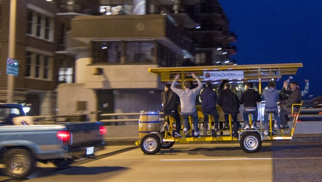 Riders on the popular Pedal Tavern travel along Water Street in the Third Ward on Oct. 5, 2012, in Milwaukee. Pedal pubs - multiple-person bicycles that ferry riders to and from taverns - have been springing up all over the country in recent years.