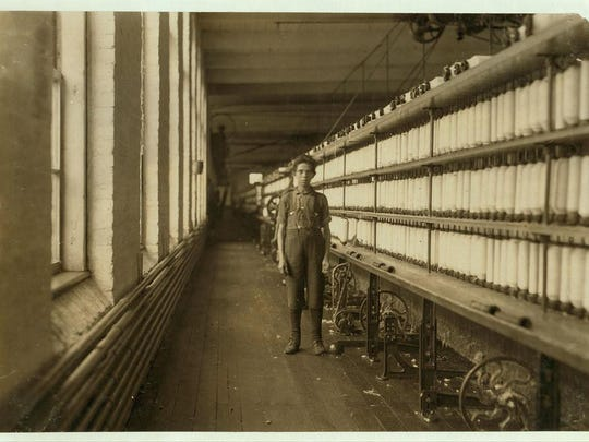 """Joe Manning's caption: Joseph Beaudoine, 14 years old. Lewis Hine's caption: Jo Bodeon. A """"back-roper"""" in mule room. Chace Cotton Mill, Burlington, Vt. May 1909."""