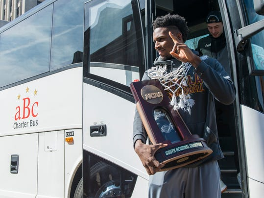Donte Ingram and his Loyola  teammates step off the bus with the NCAA South Regional Championship trophy while greeting fans and members of the press, Sunday, March 25, 2018 in Chicago. (Tyler LaRiviere/Chicago Sun-Times via AP)